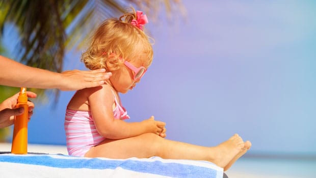 Au pair applying sunscreen to child