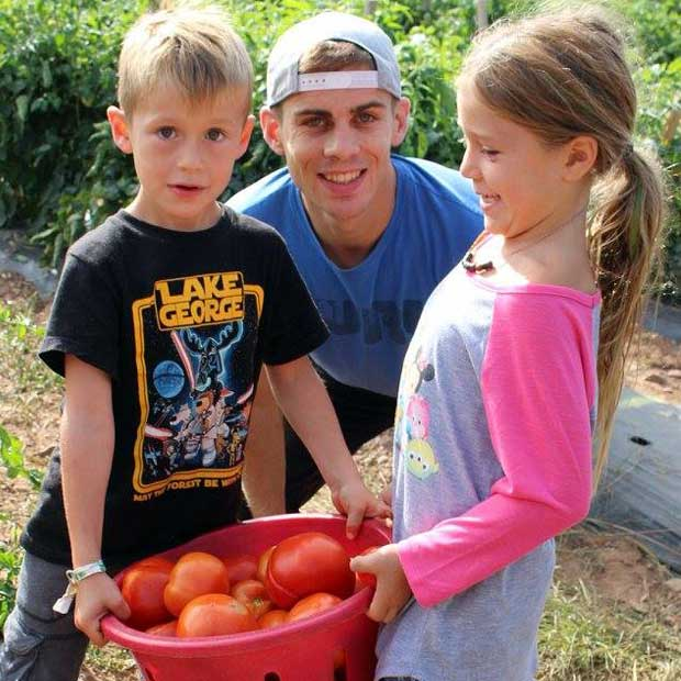Simon goes tomato picking with his host kids.