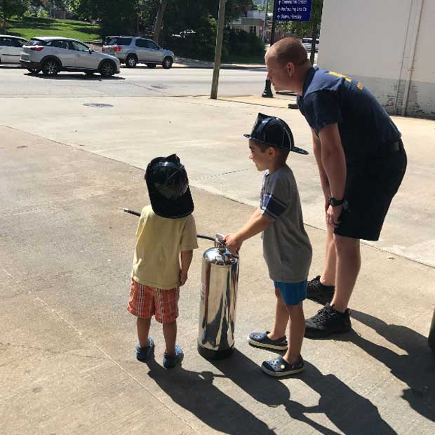 These junior firefighters pretended to fight a fire in the driveway!