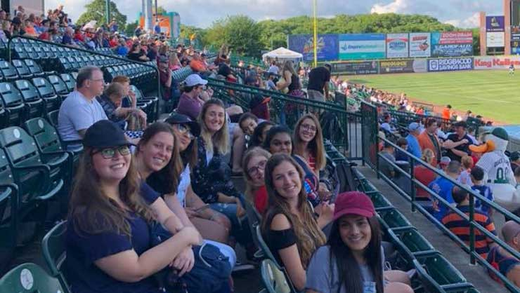 Long Island au pairs went to a baseball game.
