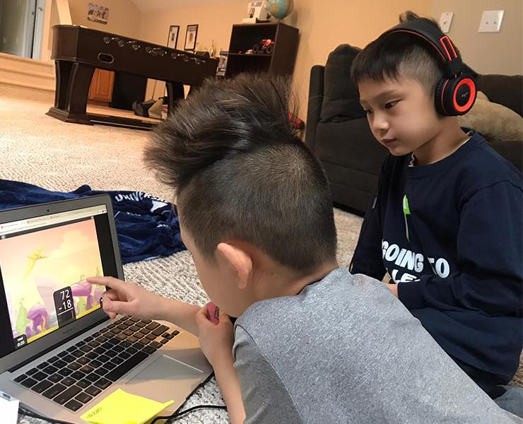Two young boys sit in front of a computer in a living room playing an educational math game