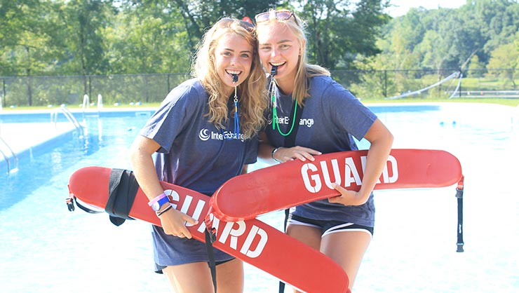 Two young women stand by a pool holding flotation devices
