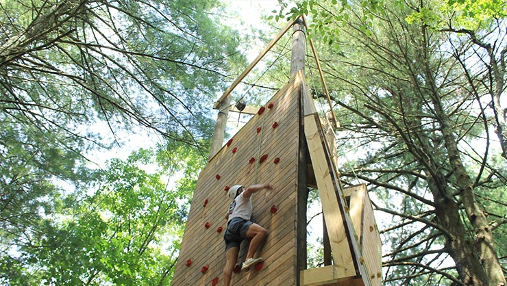 A young man ascends a climbing wall in the woods