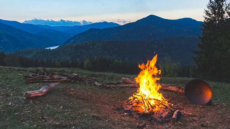 A campfire on a hill at dawn with mountains in the background