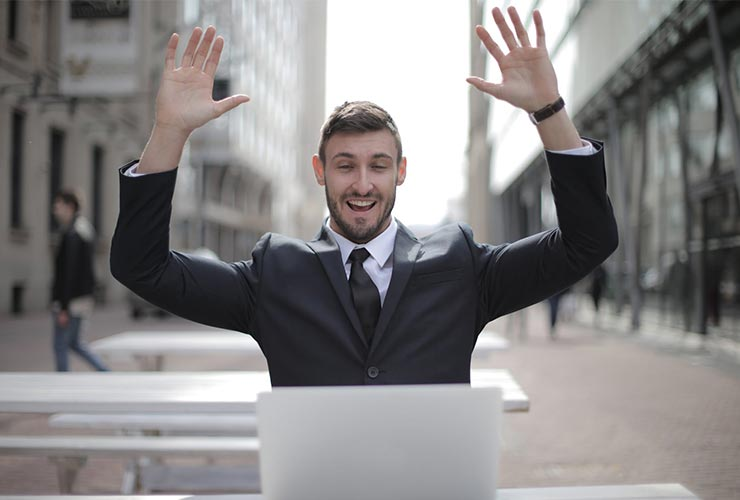 Man in suit smiles with arms over head