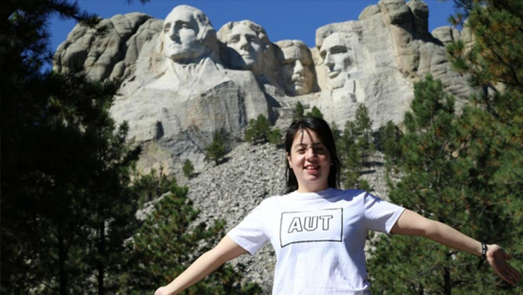 A woman stands in front of Mount Rushmore in North Dakota