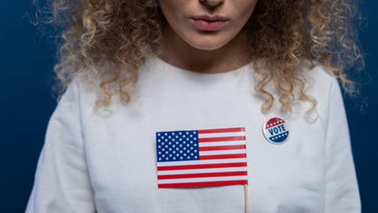 Woman with an 'I voted' pin holds American flag.