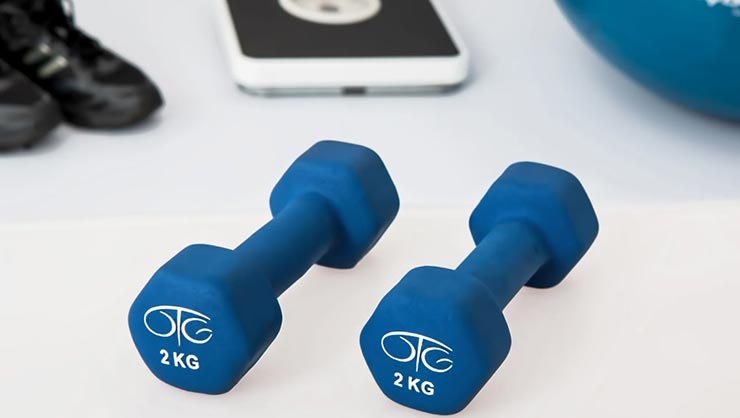 Two blue 2 kilogram barbells next to an exercise ball, a scale, and workout shoes