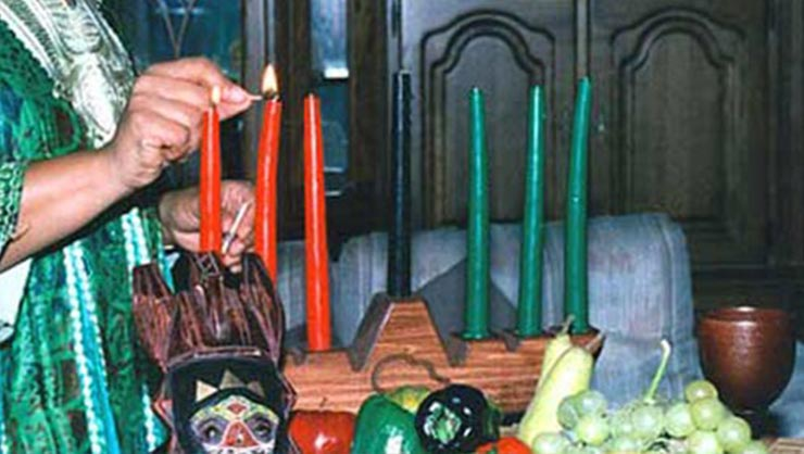 A woman lights three red candles, three green candles, and one black candle that are placed on a kinara