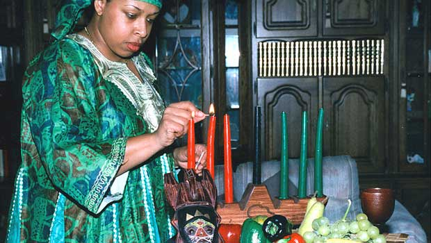 A woman celebrates Kwanzaa by lighting candles on a kinara.