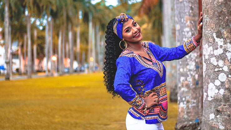 Smiling woman in blue dashiki leans on pole