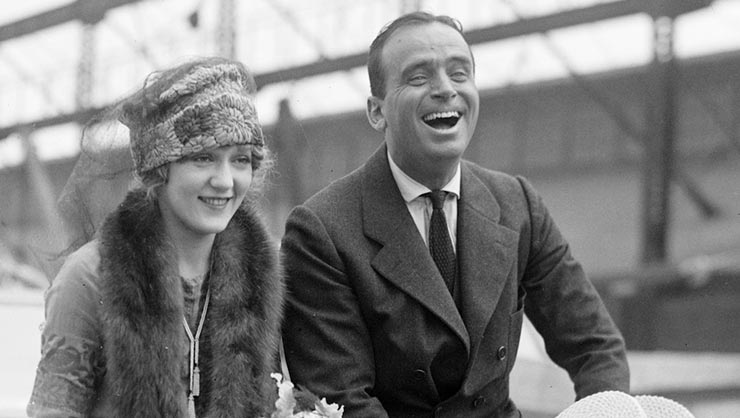 A smiling woman and man in 1920s period clothes