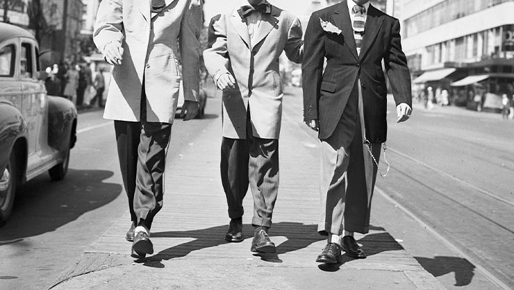 Three men in zoot suits walk down a street.