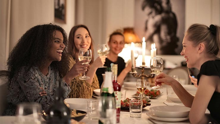 A smiling group of young women having dinner.