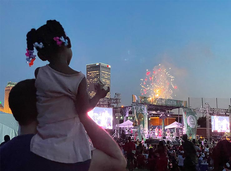 A daughter sits on her father's shoulders as they look at Juneteenth fireworks.