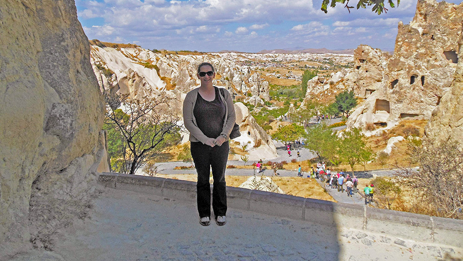 A woman stands in front of mountains in Cappadocia, Turkey