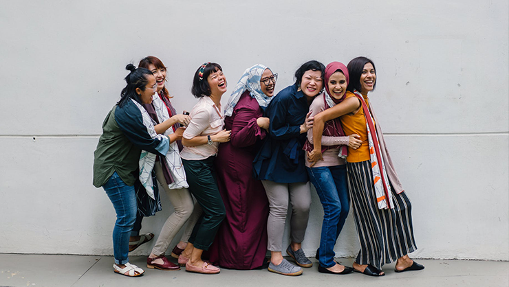 A diverse group of smiling women standing near a wall