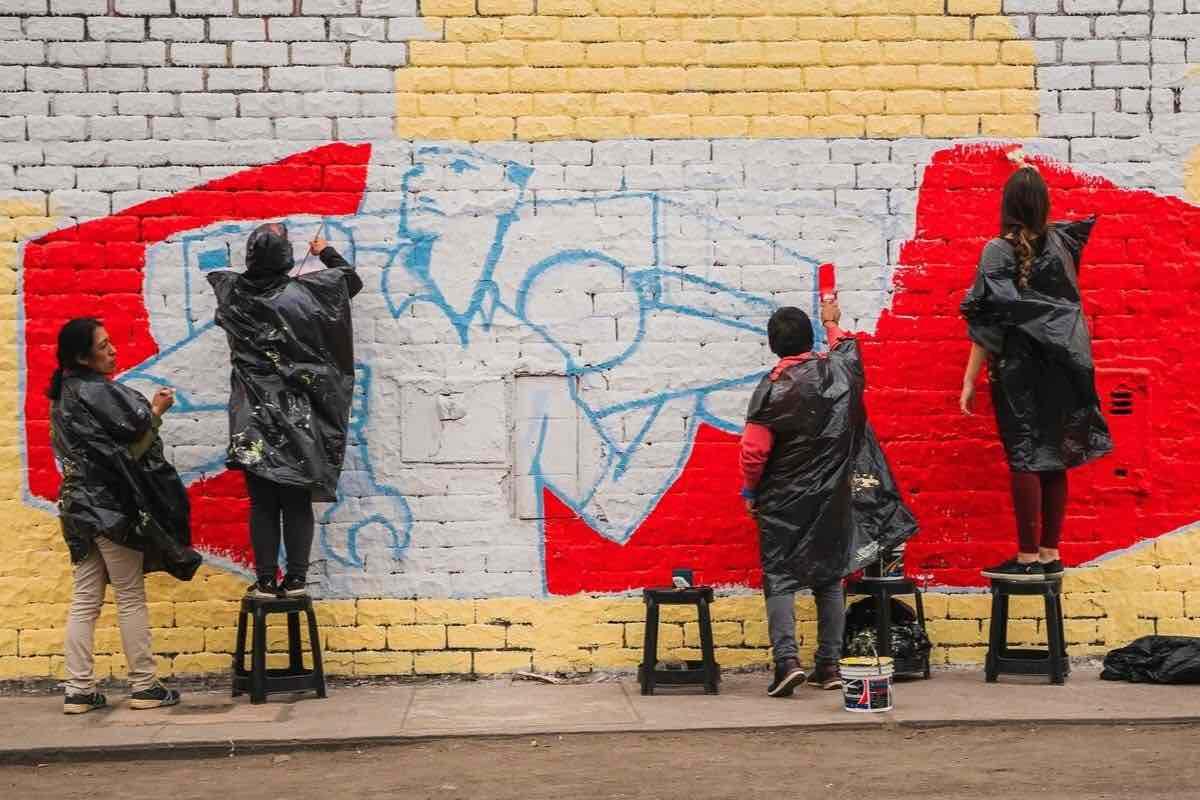 Volunteers painting a mural