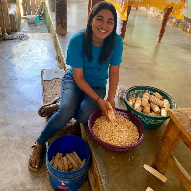 Removing freshly harvested corn from the cob at an acompañante's house in the community of Salvador Urbina