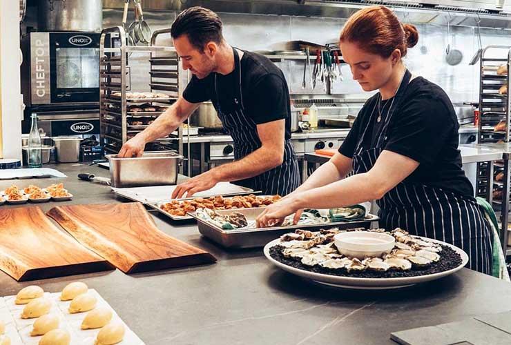 Two chefs preparing food in a restaurant kitchen