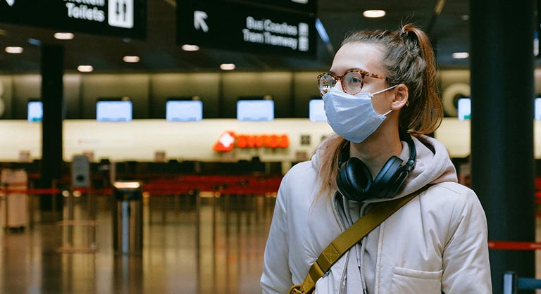 Young woman in a mask in bus terminal