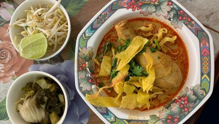 Khao soi gai: chicken stewed in a curry sauce, mixed with coconut milk, and served with egg noodles, pickled greens, and crispy noodles on top
