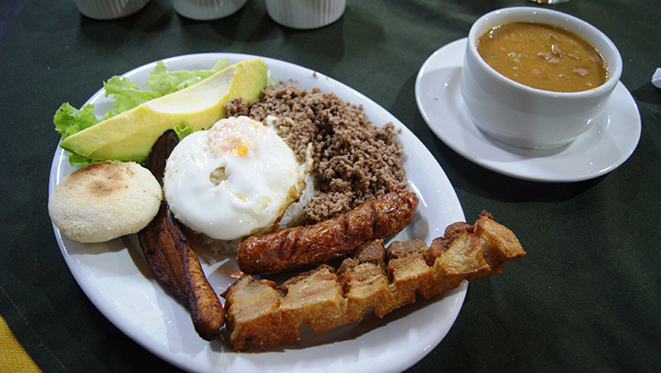 Typical Colombian bandeja paisa dish, consisting of beans, sausage, egg, avocado, pork rind, and fried plantain.