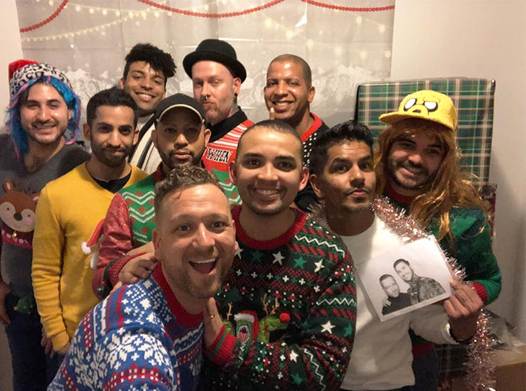 Men pose in christmas-themed sweaters