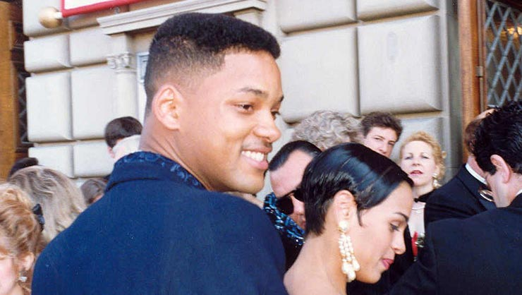 A side view of Will Smith with many people in the background
