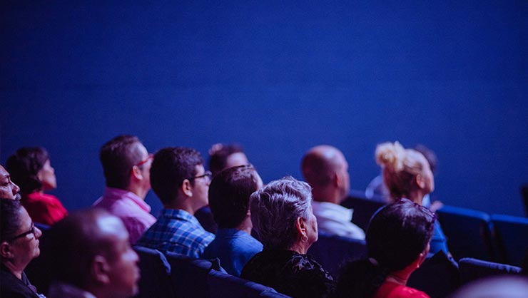 An audience sits in rows against a blue  wall
