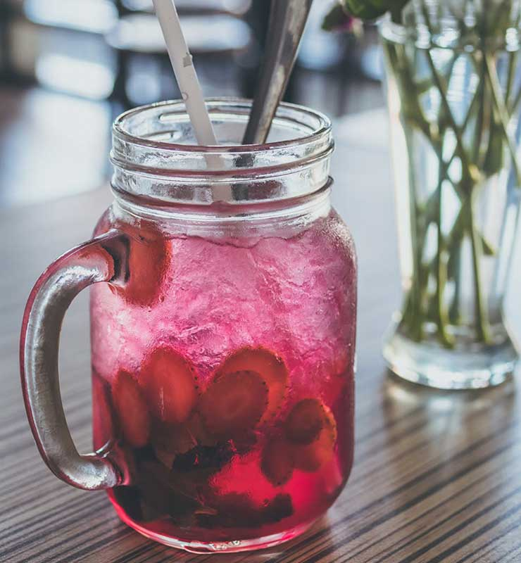 Jar of strawberry drink in mason jar with straw and spoon
