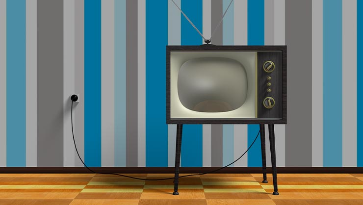 Vintage television in front of retro wallpaper