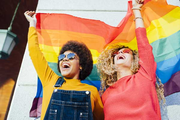 Smiling women holding a pride flag