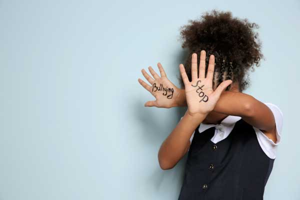 A girl hides her face and has stop bullying written on her hands