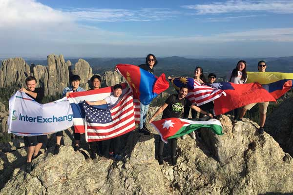 Participants hold world flags on a mountaintop