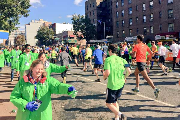 Volunteers give runners water at the NYC Marathon