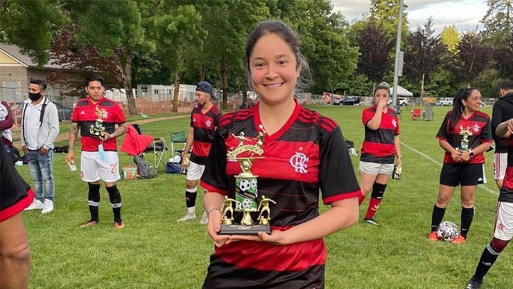 A smiling woman poses with a trophy on a soccer pitch, surrounded by her teammates.