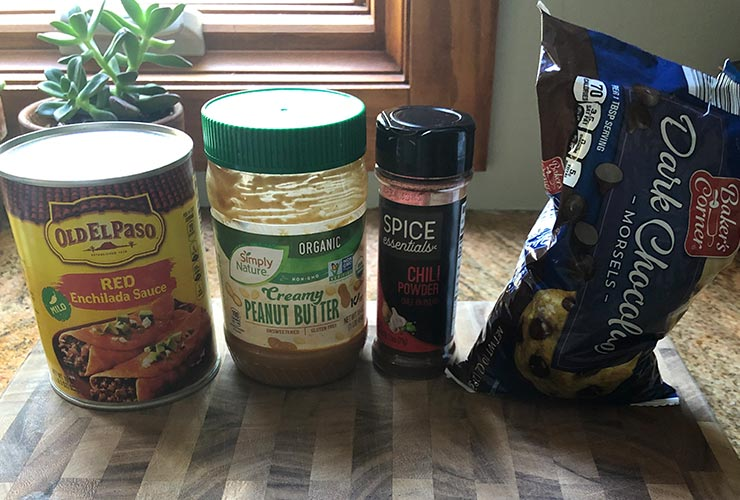 A can of enchilada sauce, a jar of peanut butter, a container of chili powder, and a bag of chocolate chips on a wooden table