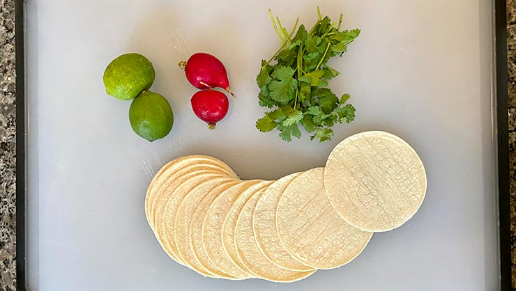 Tortillas, limes, jalapeno peppers, and cilantro on a cutting board
