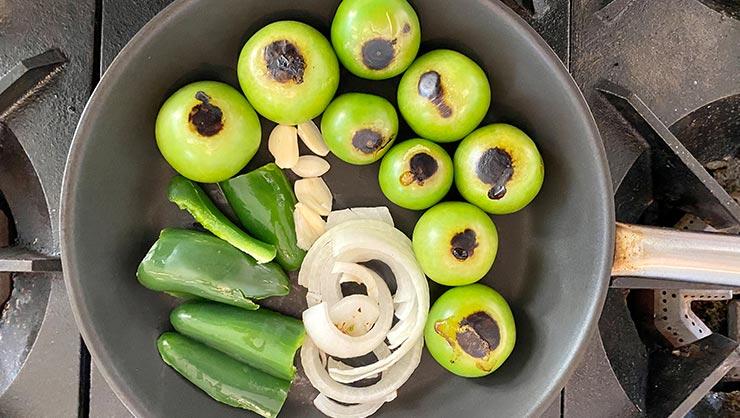Tomatillos, onion, garlic, and jalapenos on a pan