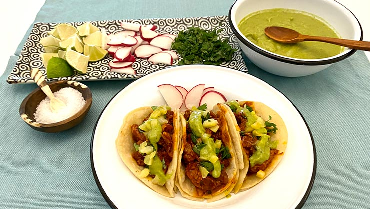 Tacos and ingredients on a plate and guacamole in a bowl