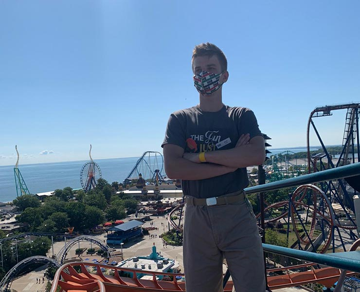 Man stands on platform in front on amusement park
