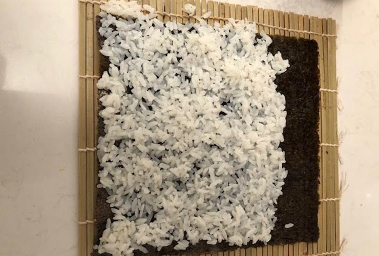 White rice and seaweed wrap on a bamboo mat