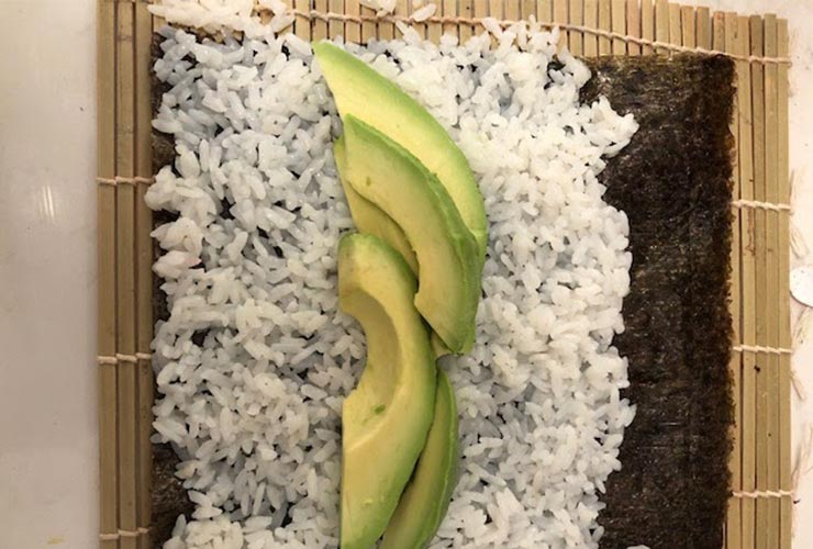 White rice, avocado slices, and seaweed wrap on a bamboo mat