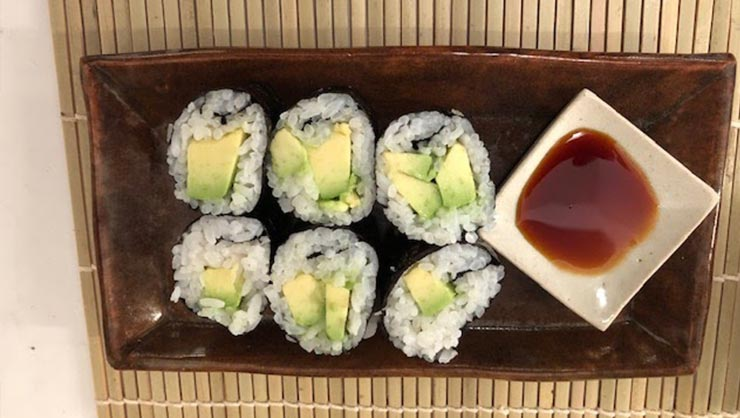 Prepared sushi and soy sauce on a bamboo mat