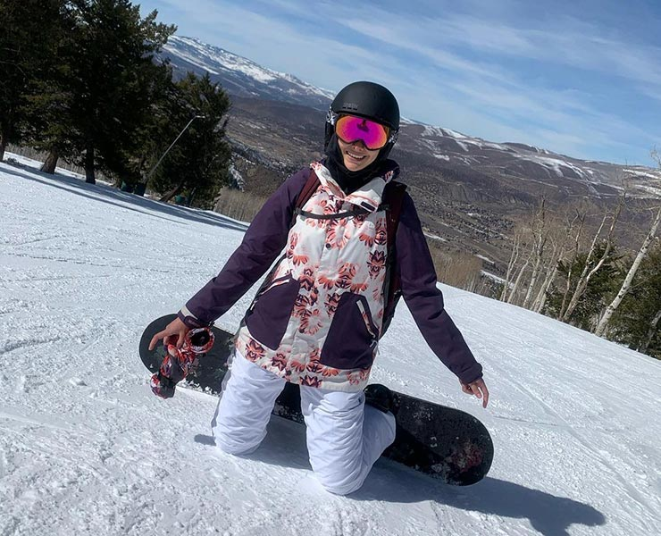 A young woman with a snowboard kneels on a snowy mountain